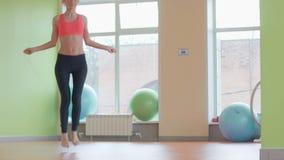 Kondition- och livsstilbegrepp - kvinna som gör sportar hoppande over white för flickaisoleringsrep lager videofilmer