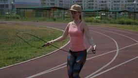 Kondition- och livsstilbegrepp - kvinna som utomhus gör sportar hoppande over white för flickaisoleringsrep arkivfilmer