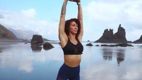 Kondition och motivation Sund idrottsman nenflicka som sträcker på stranden på solig dag Sportig kvinnlig kvinna med flätad trådu arkivfilmer