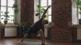Kondition och sunt livsstilbegrepp - attraktiv man som gör yoga att posera i idrottshall lager videofilmer