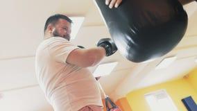 Kondition och v?rd- Boxas i idrottshall En fet man slår den stansa påsen i sportkorridor med privarelagledaren Förlust för indivi lager videofilmer