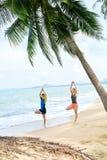 Kondition Praktiserande yoga för par på stranden öva sportar ST Arkivfoton