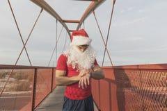 Kondition Santa Claus som ser den smarta klockan Fotografering för Bildbyråer