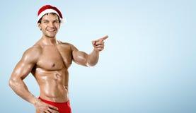 Kondition sexiga Santa Claus, showpekfinger och leende, på blått Royaltyfri Foto
