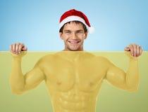 Kondition sexiga Santa Claus, ställning med det gula banret och leende Royaltyfri Bild