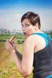 Kondition som är härlig plus formatkvinnan som äter stealthily skräpmat Royaltyfri Bild