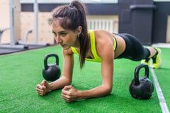 Kondition som utbildar den idrotts- sportiga kvinnan som gör plankaövning i idrottshall- eller yogagruppbegreppet som övar den ae royaltyfri fotografi