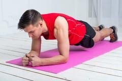 Kondition som utbildar den idrotts- sportiga mannen som gör plankan Arkivfoto