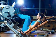Kondition, sport, bodybuilding, öva och folkbegrepp - ung kvinna som böjer muskler på benpressmaskinen i idrottshall Royaltyfri Bild