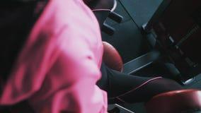 Kondition, sport, bodybuilding, öva och folkbegrepp - ung kvinna som böjer muskler på benpressmaskinen i idrottshall lager videofilmer