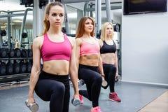 Kondition, sport, kamratskap och sunt livsstilbegrepp - grupp av attraktiva unga kvinnor som gör utfall med vikter i idrottshalle Arkivfoto