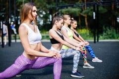 Kondition, sport, kamratskap och sunt livsstilbegrepp - grupp av attraktiva unga kvinnor som utomhus gör utfallet Arkivbilder