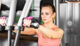 Kondition, sport, powerlifting och folkbegrepp - sportig kvinna som gör genomkörare i idrottshall Royaltyfri Foto