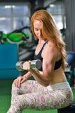 Kondition sport som övar livsstil - den attraktiva unga kvinnan som gör att lyfta för vikt, övar på biceps på idrottshallen arkivbilder