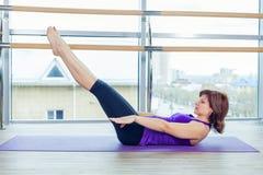 Kondition, sport, utbildning och folkbegrepp - le kvinnan som gör buk- övningar på mattt i idrottshall royaltyfri fotografi