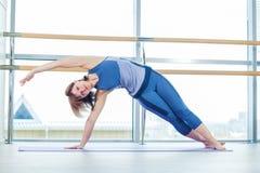 Kondition, sport, utbildning och folkbegrepp - le kvinnan som gör buk- övningar på mattt i idrottshall arkivbilder