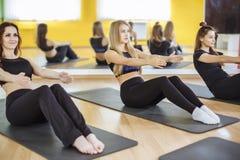 Kondition-, sport-, utbildnings-, idrottshall- och livsstilbegrepp - grupp av att le kvinnor som övar på mats i idrottshallen Royaltyfri Foto