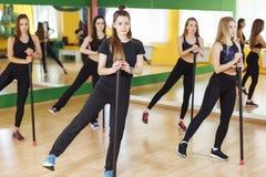 Kondition-, sport-, utbildnings-, idrottshall- och livsstilbegrepp - grupp av kvinnor som övar i idrottshall Arkivbild