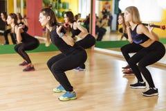 Kondition-, sport-, utbildnings-, idrottshall- och livsstilbegrepp - grupp av kvinnor som övar med stänger i idrottshall Fotografering för Bildbyråer