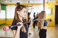 Kondition-, sport-, utbildnings-, idrottshall- och livsstilbegrepp - grupp av kvinnor som övar med stänger i idrottshall Royaltyfri Fotografi