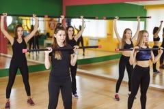 Kondition-, sport-, utbildnings-, idrottshall- och livsstilbegrepp - grupp av kvinnor som utarbetar med skivstånger i idrottshall Arkivbilder