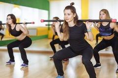 Kondition-, sport-, utbildnings-, idrottshall- och livsstilbegrepp - grupp av kvinnor som utarbetar med skivstånger i idrottshall Royaltyfria Foton