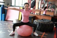 Kondition-, sport-, utbildnings-, idrottshall- och livsstilbegrepp - ung kvinna som gör övning på konditionboll Utrustning medite Royaltyfri Fotografi