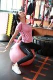 Kondition-, sport-, utbildnings-, idrottshall- och livsstilbegrepp - ung kvinna som gör övning på konditionboll Utrustning medite Royaltyfri Foto
