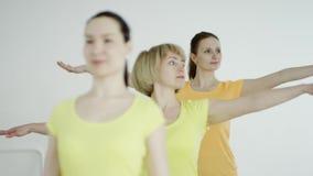 Kondition-, sport-, utbildnings- och livsstilbegrepp - grupp av att le kvinnor som sträcker i idrottshall lager videofilmer