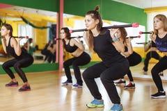 Kondition-, sport-, utbildnings- och livsstilbegrepp - grupp av kvinnor med skivstånger i idrottshall Royaltyfria Foton