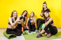 Kondition-, sport-, utbildnings- och livsstilbegrepp - grupp av unga lyckliga kvinnor som visar tummar upp i idrottshall Arkivbild
