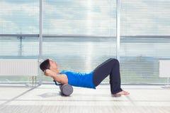 Kondition-, sport-, utbildnings- och livsstilbegrepp - kvinna som gör pilates på golvet med skumrullen royaltyfri bild