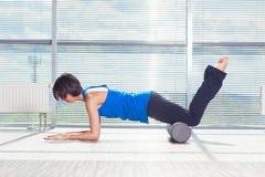 Kondition-, sport-, utbildnings- och livsstilbegrepp - kvinna som gör pilates på golvet med skumrullen royaltyfri foto