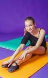 Kondition-, sport-, utbildnings- och livsstilbegrepp - le kvinnan som gör övningar på mattt i idrottshall Arkivbild