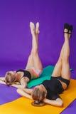 Kondition-, sport-, utbildnings- och livsstilbegrepp - le två sportiga kvinnor som gör övningar på mattt i idrottshall Royaltyfria Bilder