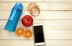 Konditionbegrepp, övning för förlorande vikt med sportuppsättningen, måttband, smart telefon som dricker flaskan, ny frukt på den Royaltyfri Fotografi