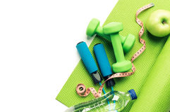 Konditionbegrepp - matt yoga, äpple, hantlar och överhopprep Royaltyfri Foto