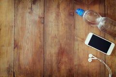 Konditionbegrepp med flaskan av vatten, mobiltelefon med hörlurar över träbakgrund Filtrerad bild Arkivfoton