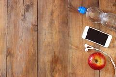 Konditionbegrepp med flaskan av vatten, mobiltelefonen med hörlurar och äpplet över träbakgrund Filtrerad bild Arkivfoto