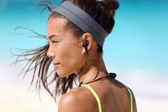 Konditionflicka med hörlurar för sporti-öra radio arkivbild