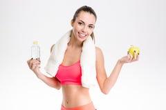 Konditionflicka med handdukinnehavflaskan av vatten och äpplet Fotografering för Bildbyråer