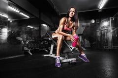 Konditionflicka med shaker som poserar på bänk i idrottshallen Fotografering för Bildbyråer