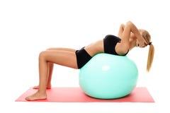 Konditionflicka som gör abs på en idrottshallboll Arkivfoto