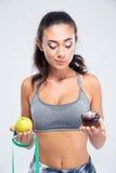 Konditionflicka som väljer mellan äpplet och kakan Royaltyfri Foto