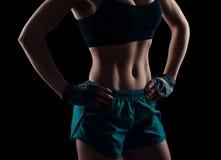 Konditionflickan i sportswearen som av visar henne formade perfekt, den brunbrända magen Sexig slank passformkvinnakropp arkivfoton