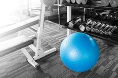 Konditionidrottshall med bollen, dumbell och annan utrustning med att skina royaltyfri fotografi