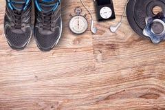 Konditionidrottshall och rinnande utrustning Hantlar och rinnande skor, parallell stoppur och musikspelare Royaltyfri Bild