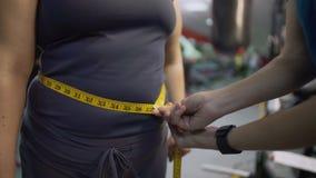 Konditioninstruktören som mäter den kvinnliga buken som är sund bantar, och genomkörareresultatkontroll arkivfilmer