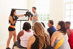 Konditioninstruktören Addressing Overweight People på bantar klubban Royaltyfri Bild