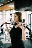 Konditionkvinna i idrottshallen Den unga kvinnan som gör kondition, övar i idrottshallen med latmaskinen Arkivfoto